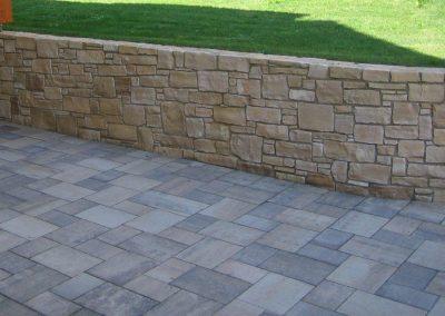 Kalksteinmauer und Betonpflaster schattiert